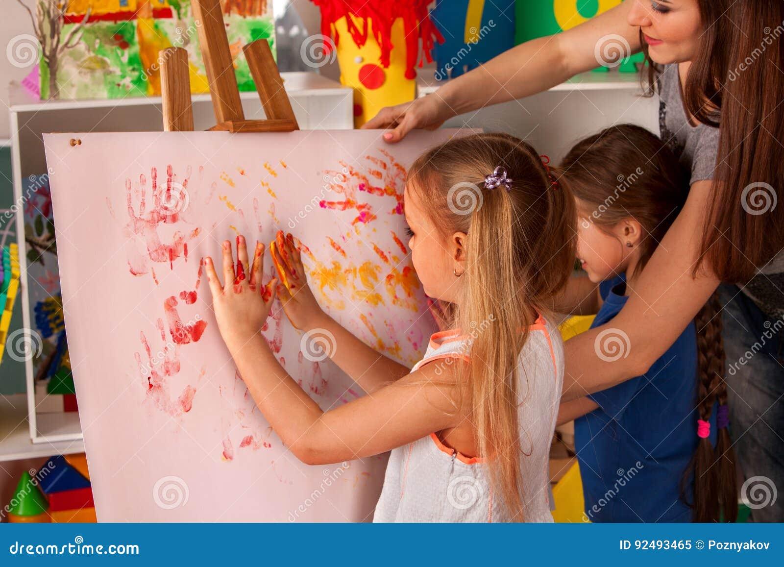 Children Painting Finger On Easel. Group Of Kids With Teacher. Stock ...