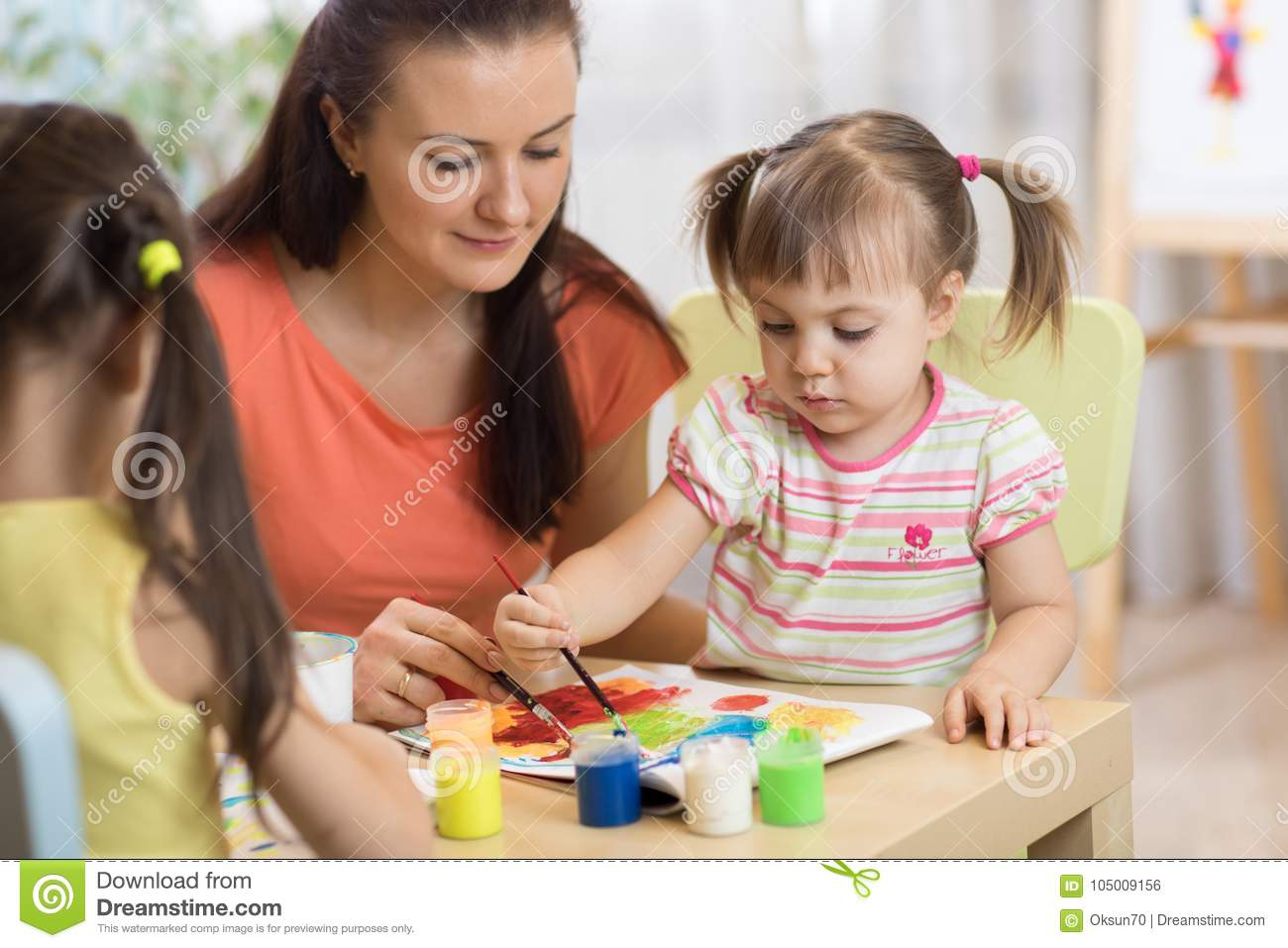Children painting in preschool. Teacher helps by little girl.