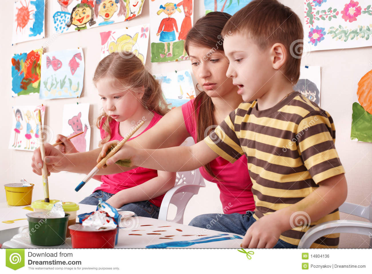 children painting with teacher in art class royalty free