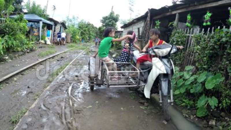 Children play riding on tricycle fell on muddy canal