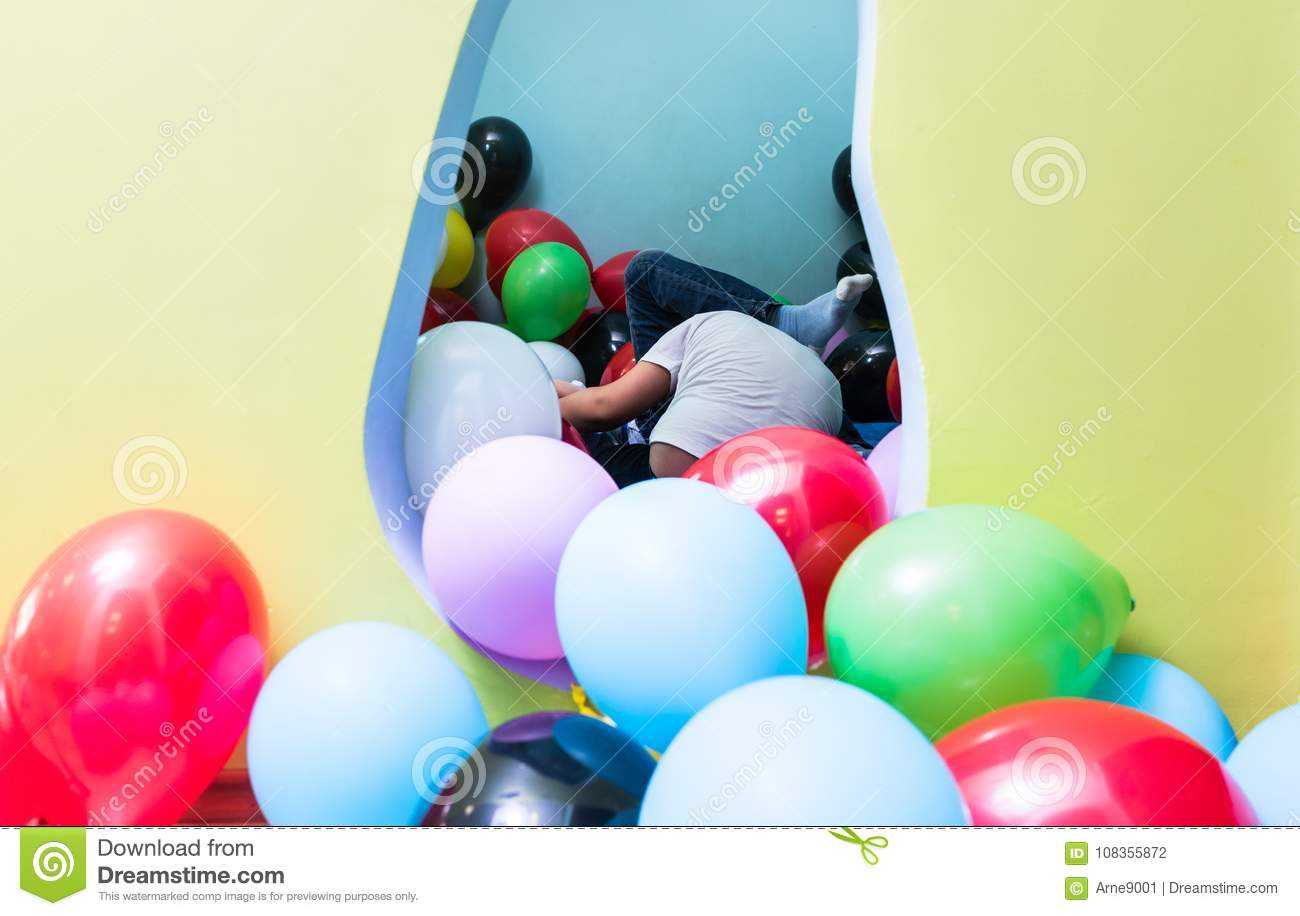 Children playing with balloons during playtime in interior of ki