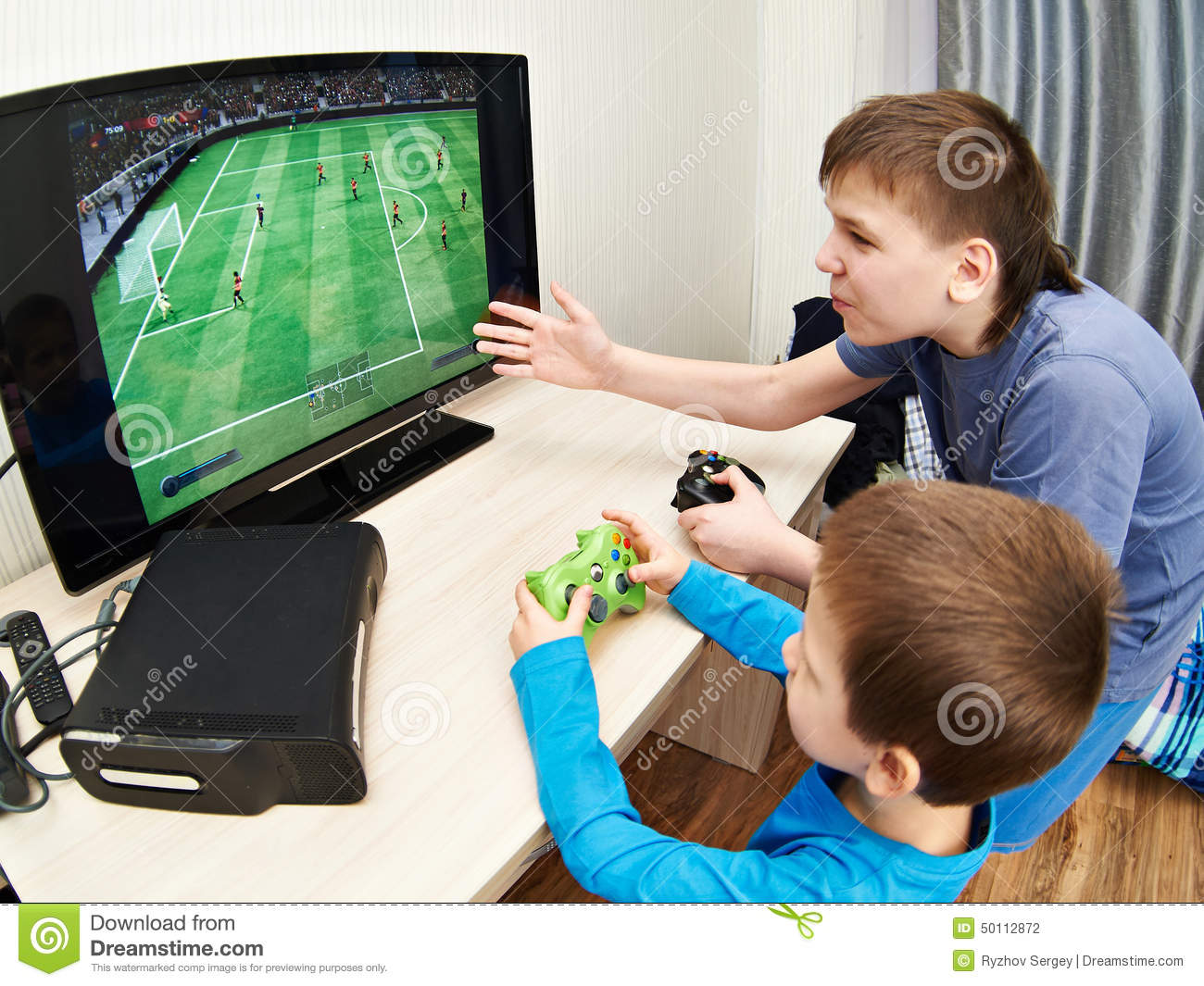Children playing on games console to play football stock for Sillas para jugar xbox