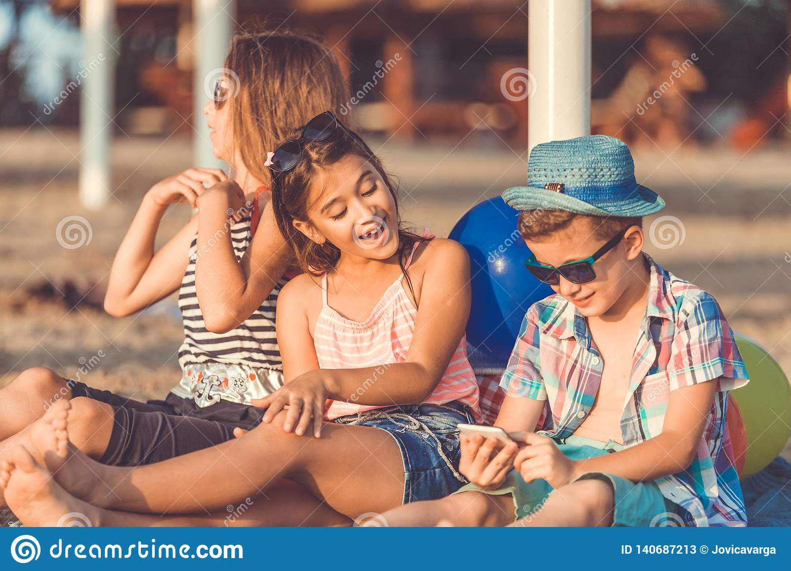 Children Playing Online Games Together On Sandy Beach Stock