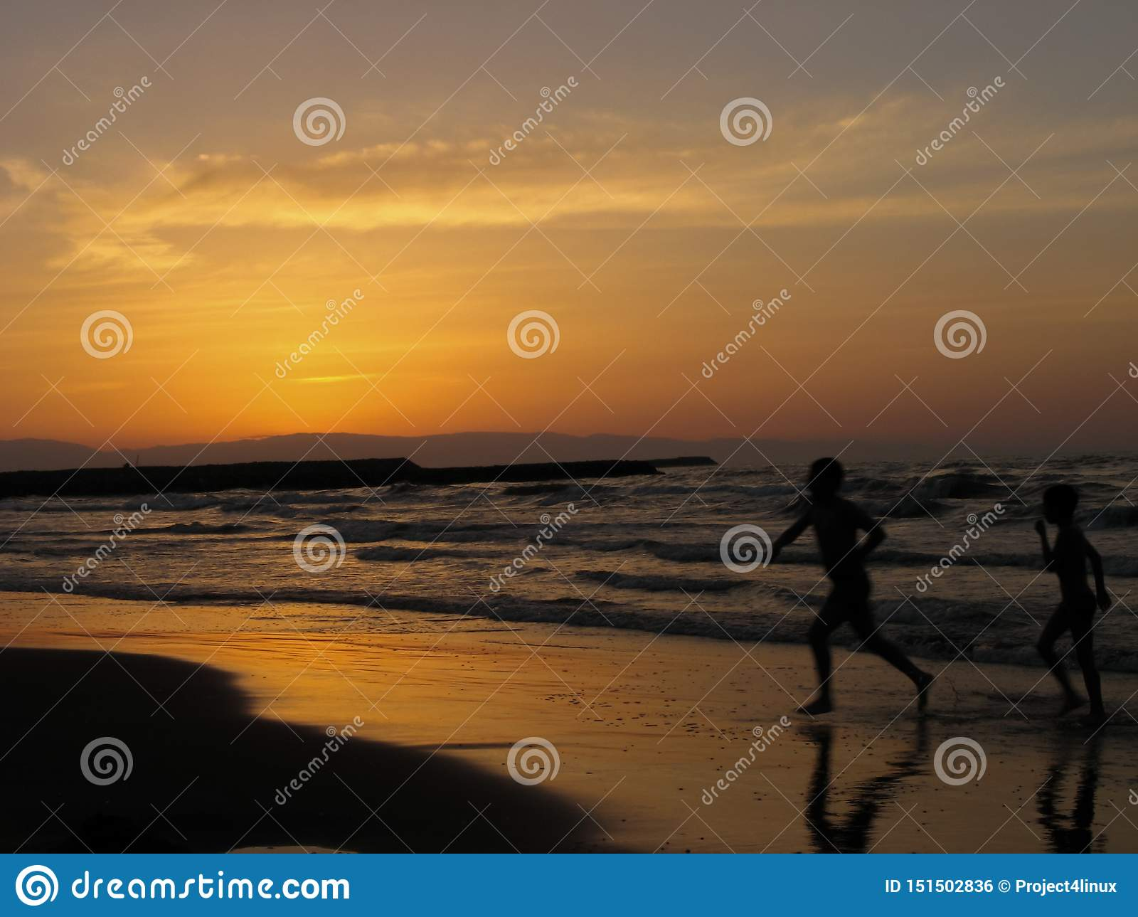 Children playing sea beach sunset. Two boys running on the beach at the sunset time