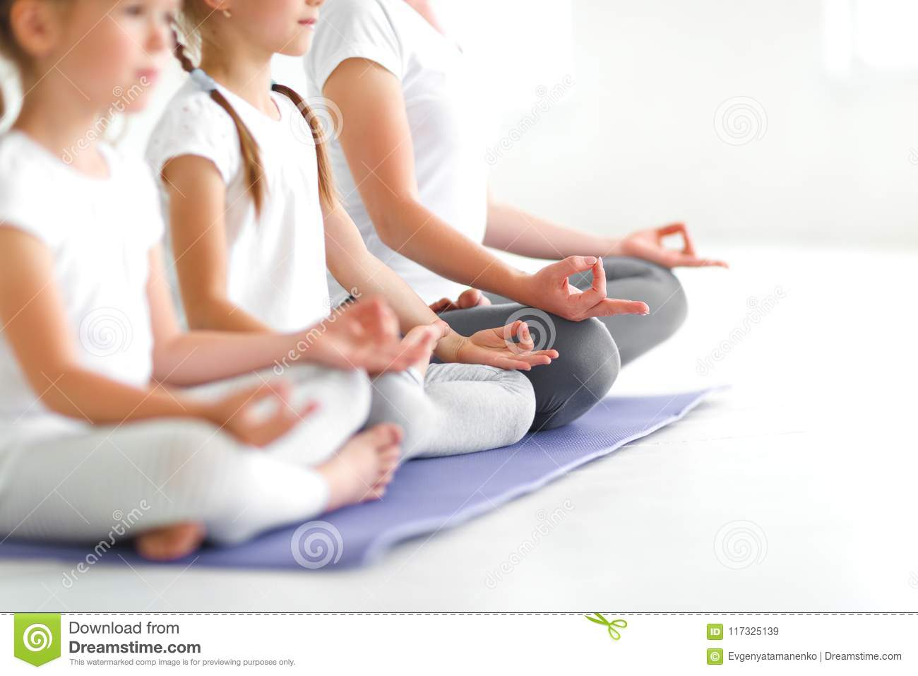 Children Practicing Yoga In A Lotus Pose With Teacher ...