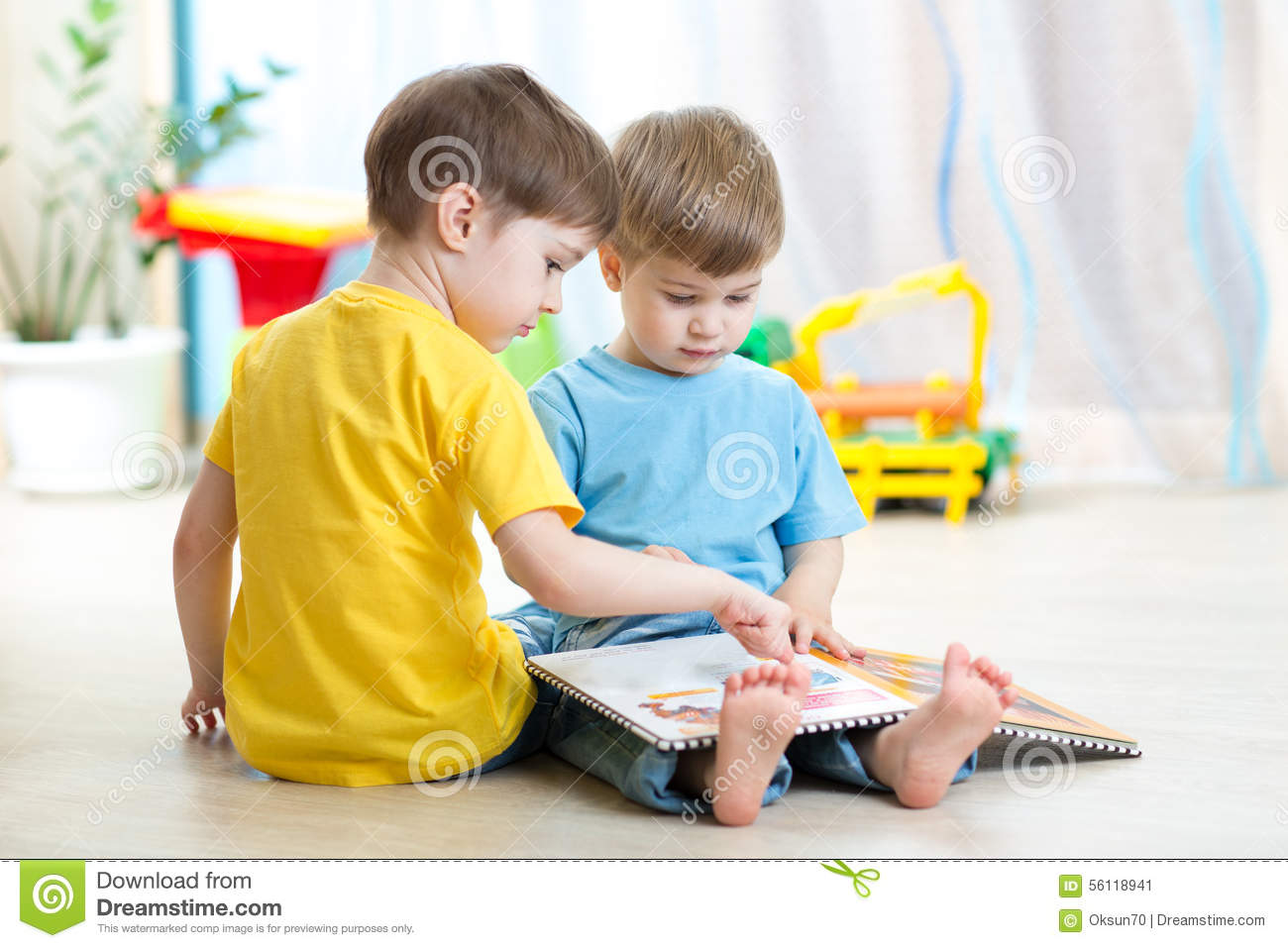 Childcare Floor Plans Children Read A Book Sitting On Floor At Home Stock Photo