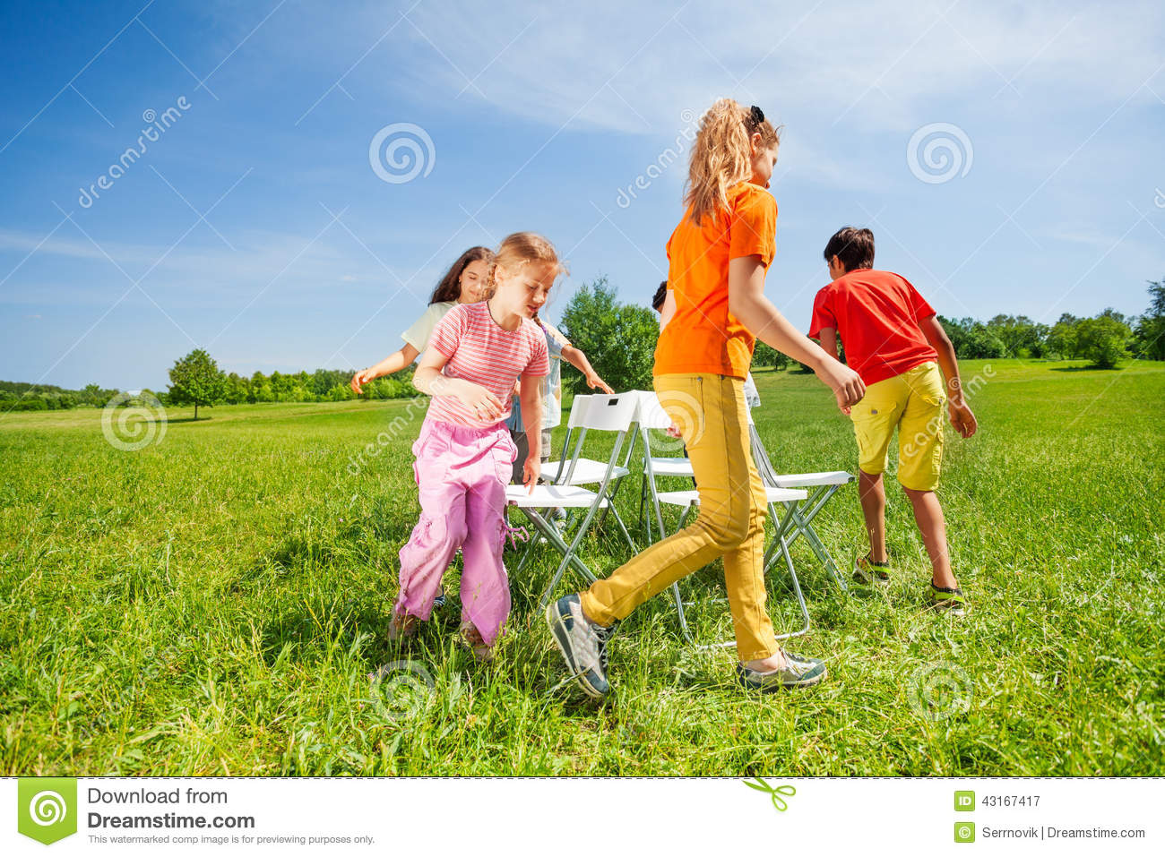 Children Run Around Chairs Playing A Game Outside Stock