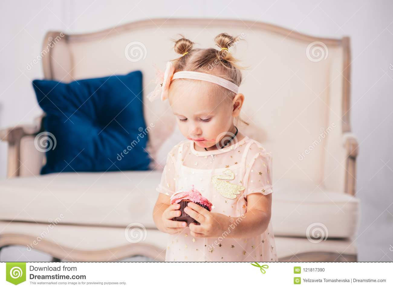 Children`s birthday. funny two-year-old Caucasian girl in pink dress standing to bedroom of house the background of couch and eat