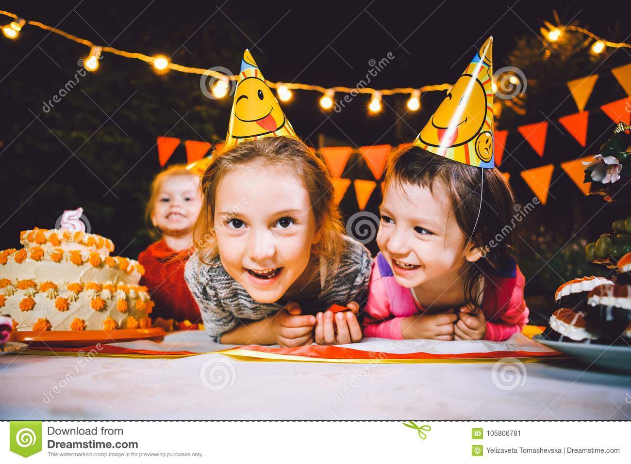 Children`s birthday party. Three cheerful children girls at the table eating cake with their hands and smearing their face. Fun a