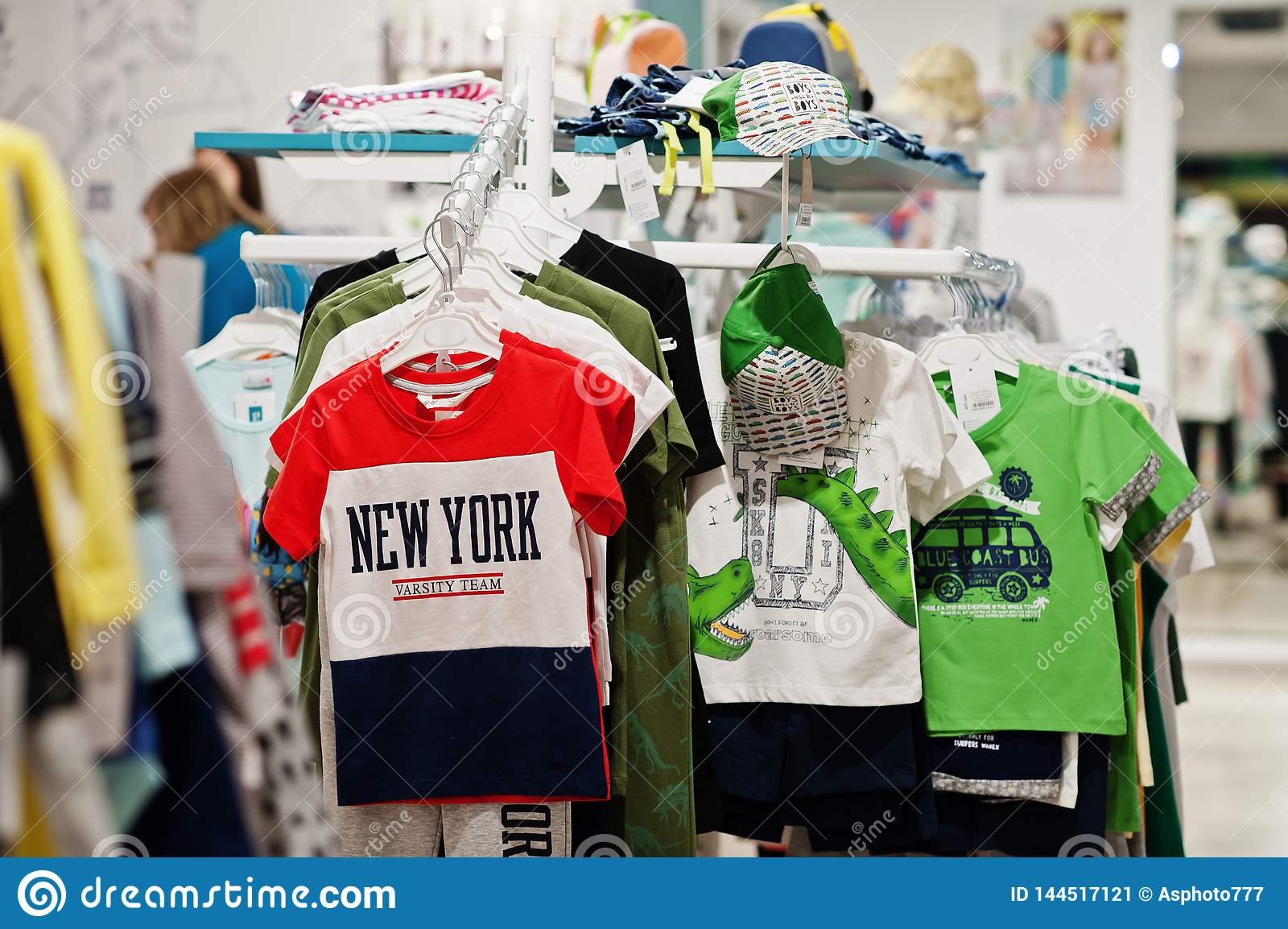 fb98f542b Children`s bright clothes hang on the display in the baby clothing store.  Boys section.