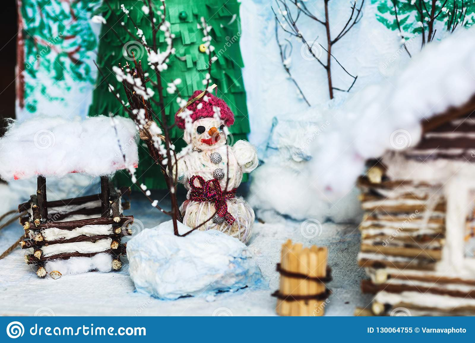 Children`s crafts of the winter yard in the snow: house, trees, well, snowman.