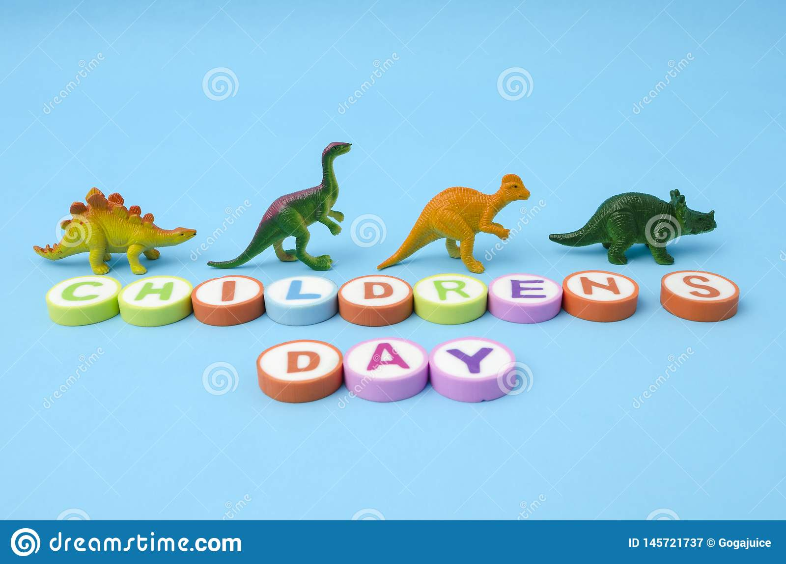 Children`s Day made from colorful letters and plastic dinosaur toys