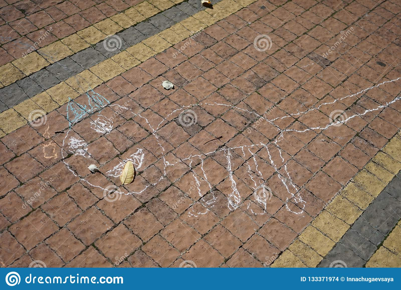 Children`s drawing a rainbow and a heart. Drawings in the park on asphalt