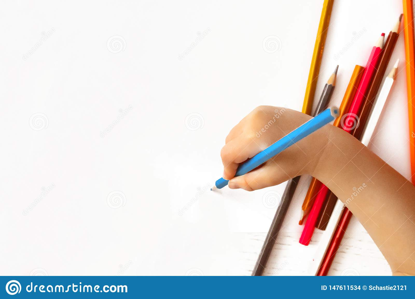 Children`s hand draws a pencil on white paper.