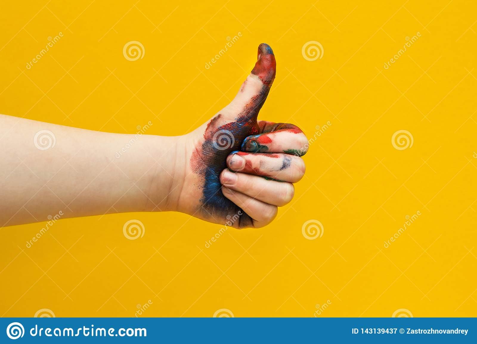 Children`s hand, smeared with multicolored paint on a yellow background. Thumbs up