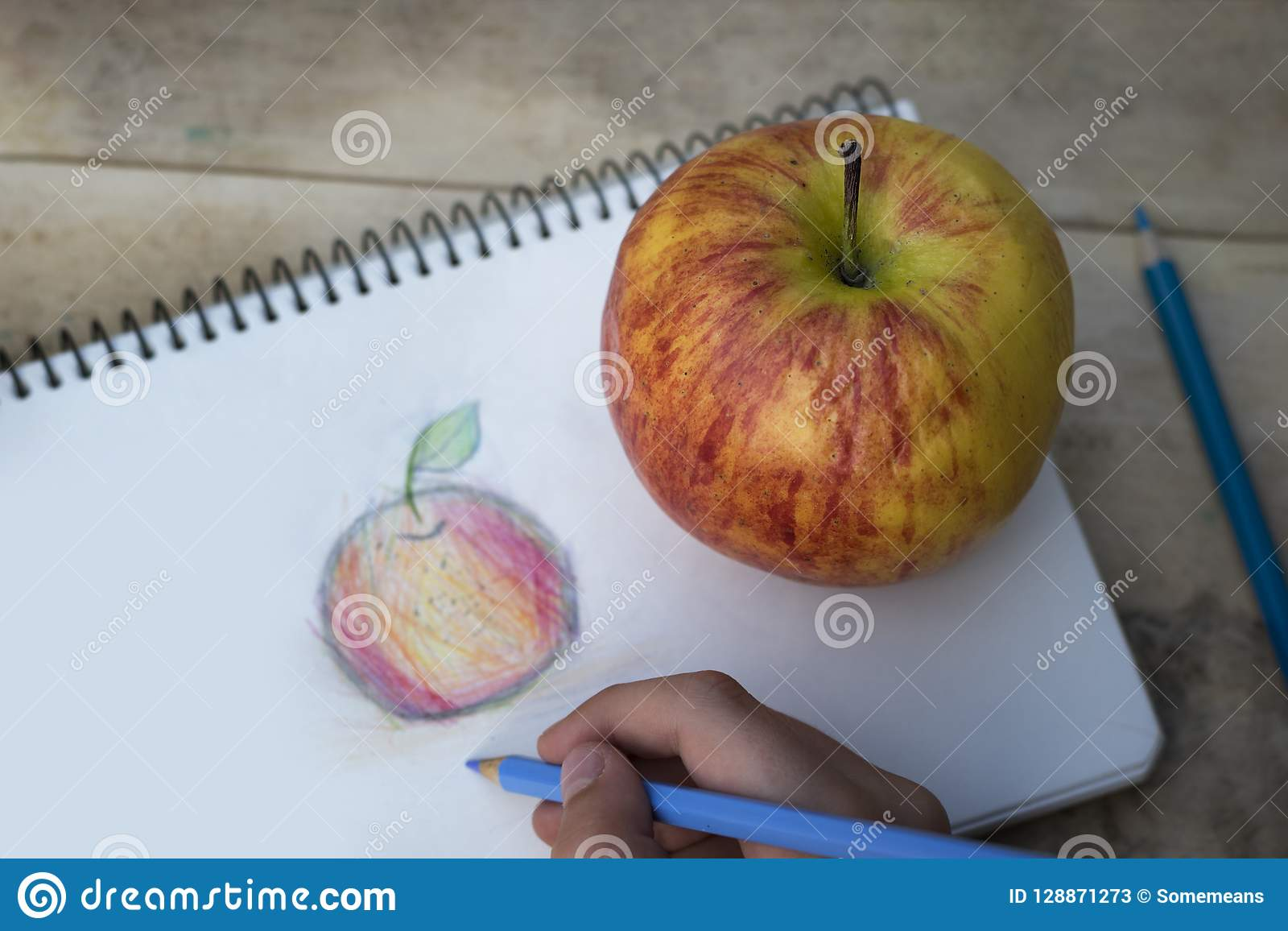 Childrens hands draw an apple with colored pencils top view