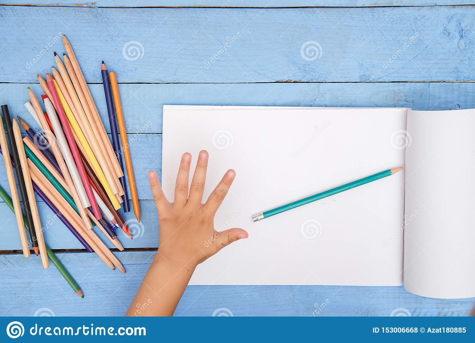 Children`s hands draw with pencils in the album on the blue table