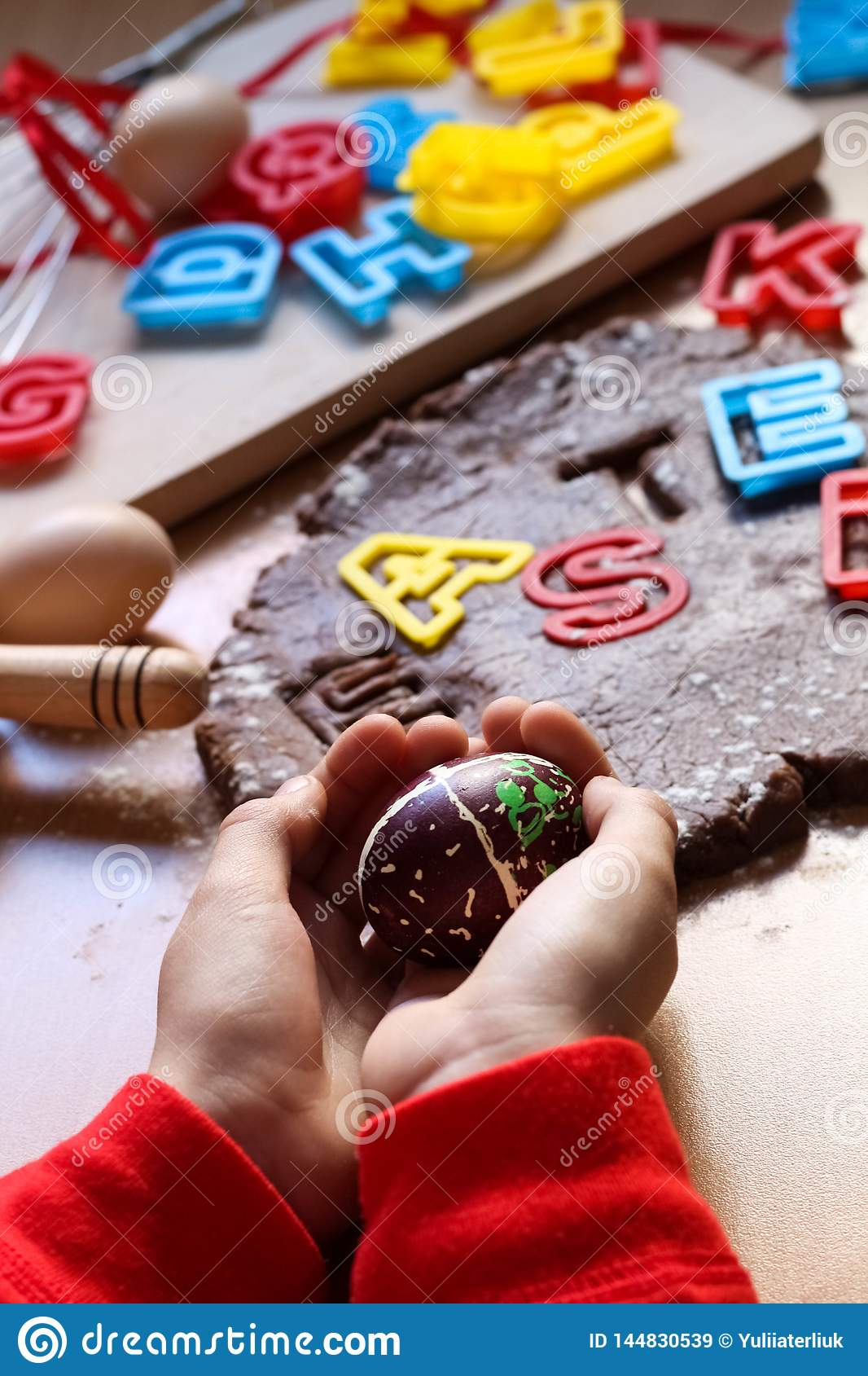 Children`s hands hold a decorated Easter egg. Cooking traditional Easter biscuits. Easter eggs. Easter food concept