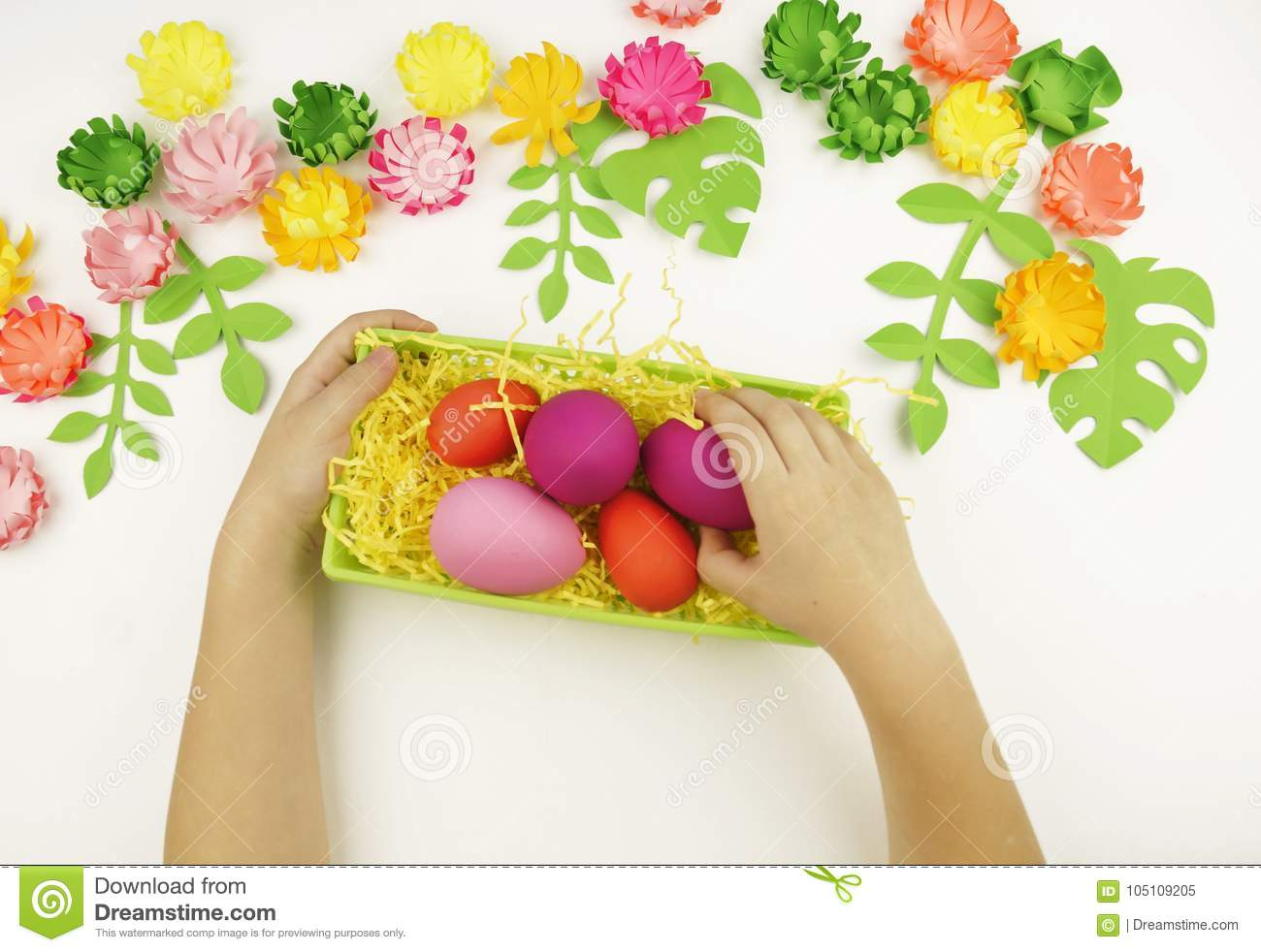 Childrens hands put easter eggs in a green basket easter childrens hands put easter eggs in a green basket easter preparation for the easter partyper flowers and leaves mightylinksfo