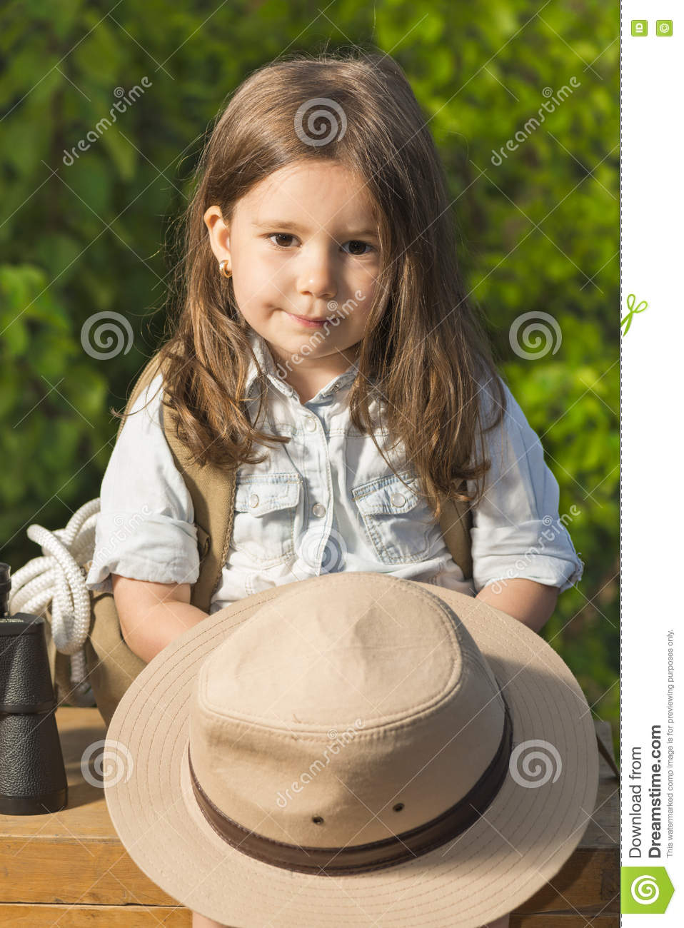 ecb0c423c4525 Adorable little girl in a safari hat and explorer clothes playing safari  sitting on wooden suitcase outdoor. Looking for the summer vacation
