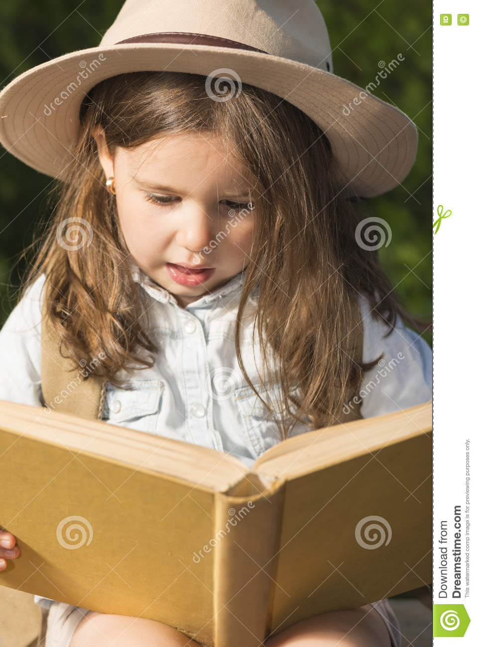 bfb7a25490b2f Adorable little girl in a safari hat and explorer clothes reading old book  sitting in a wooden suitcase with backpack and safety rope outdoor