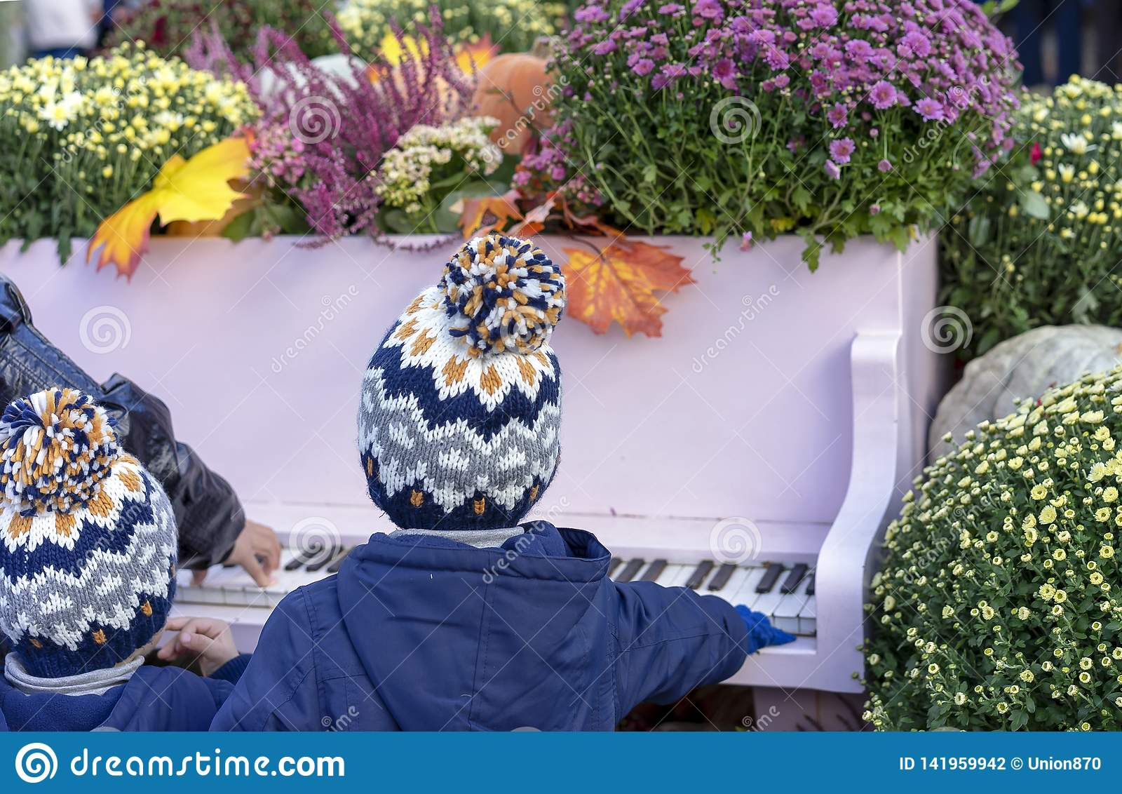 Children in the same hats playing the piano in the autumn garden