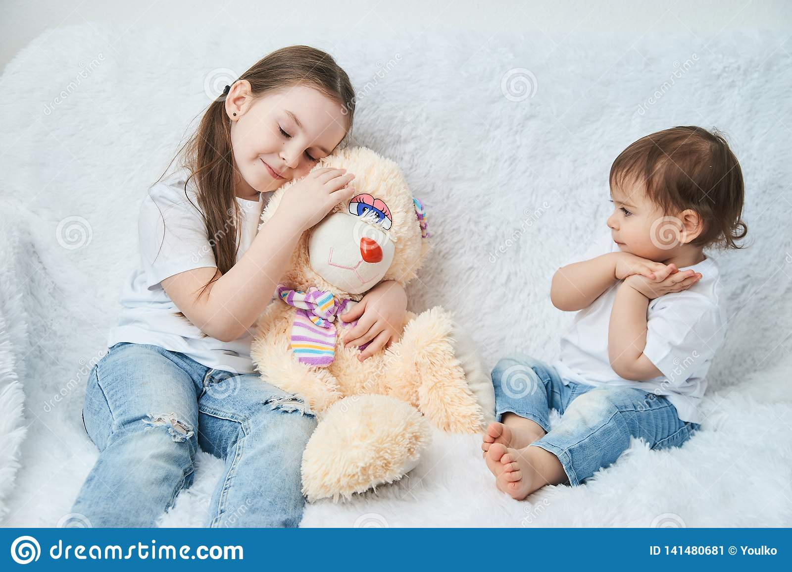 Two children, sisters play on a white sofa in white t-shirts and blue jeans. Soft plush Bunny