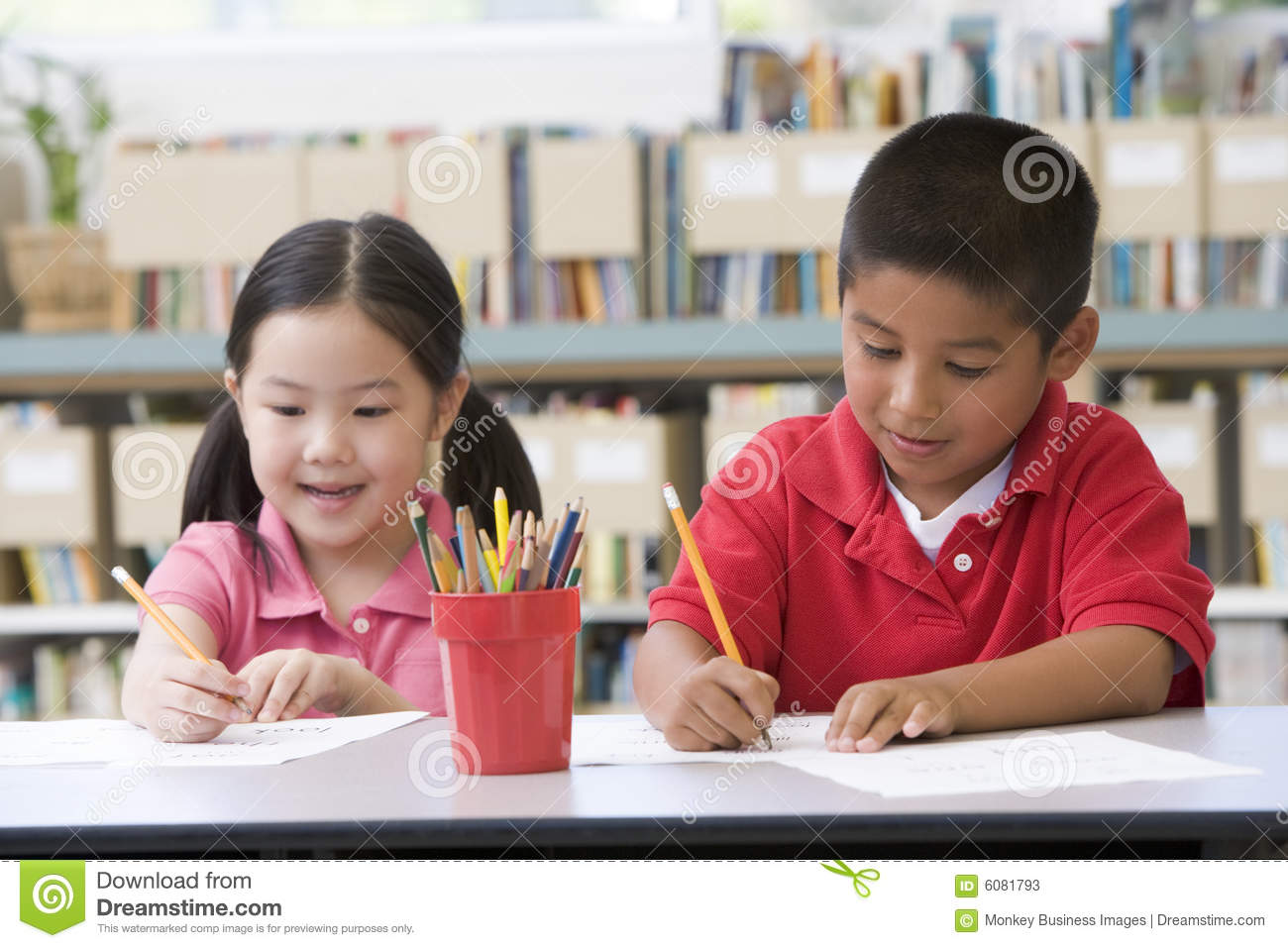 Elementary Classrooms Writing : Children sitting at desk and writing in classroom stock
