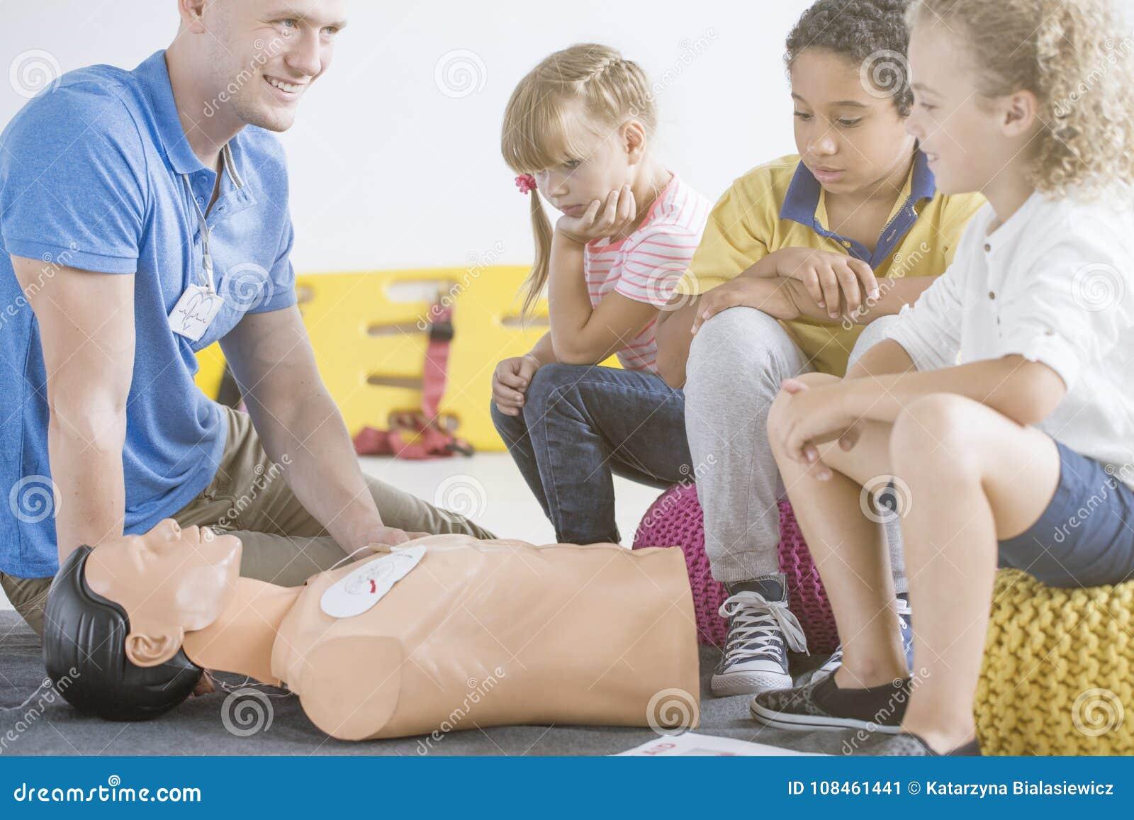 Paramedic showing defibrillator on manikin