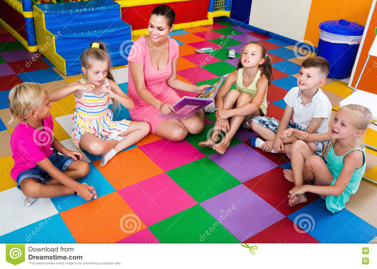 Children sitting with smiling teacher and listening to book