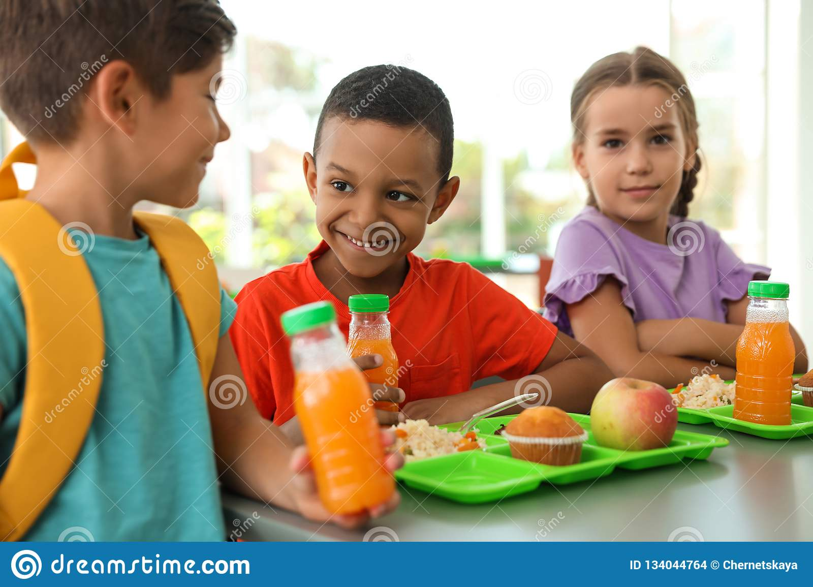Children sitting at table and eating healthy food during break