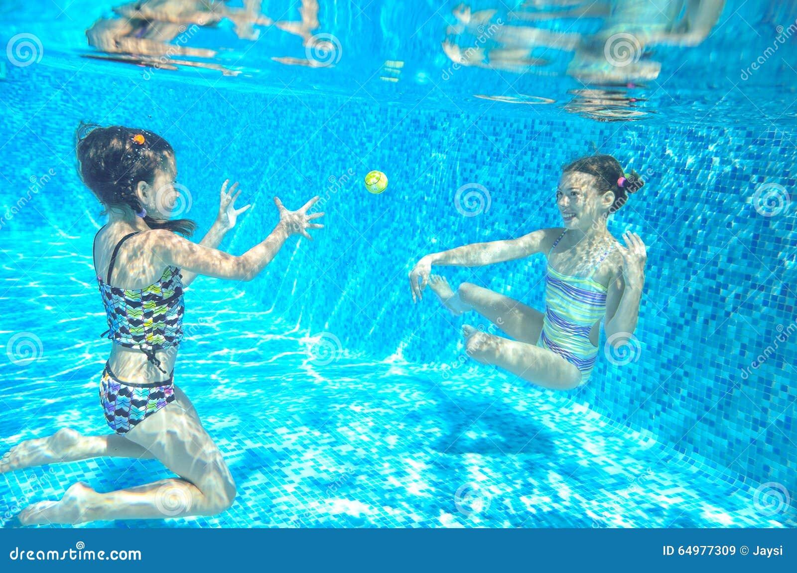 Children swim in pool underwater, happy active girls have fun under water, kids sport