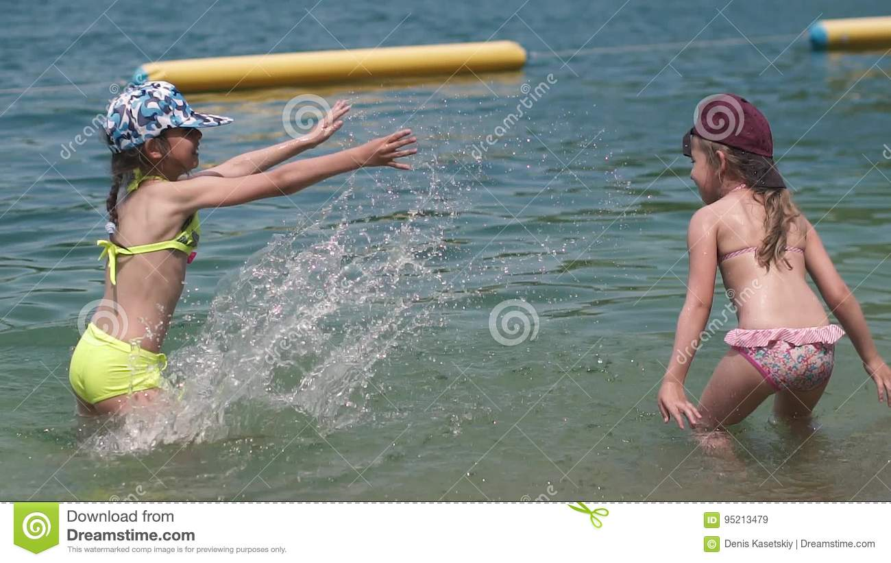 f351137613a0 Children Swim In The River And Splashing Water. Two Little Girls Enjoy Rest  By The Water. Kids Having Fun In Water Stock Video - Video of kids, ...