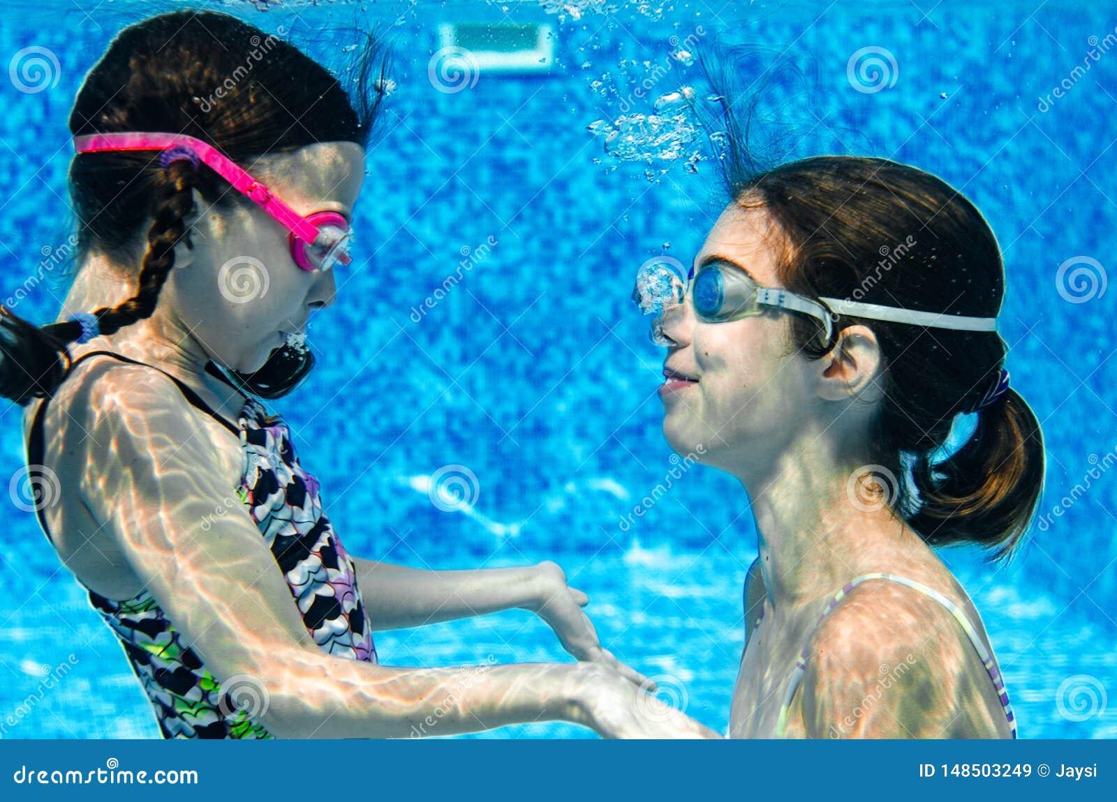 Children swim in swimming pool underwater, happy active girls have fun under water, kids fitness and sport