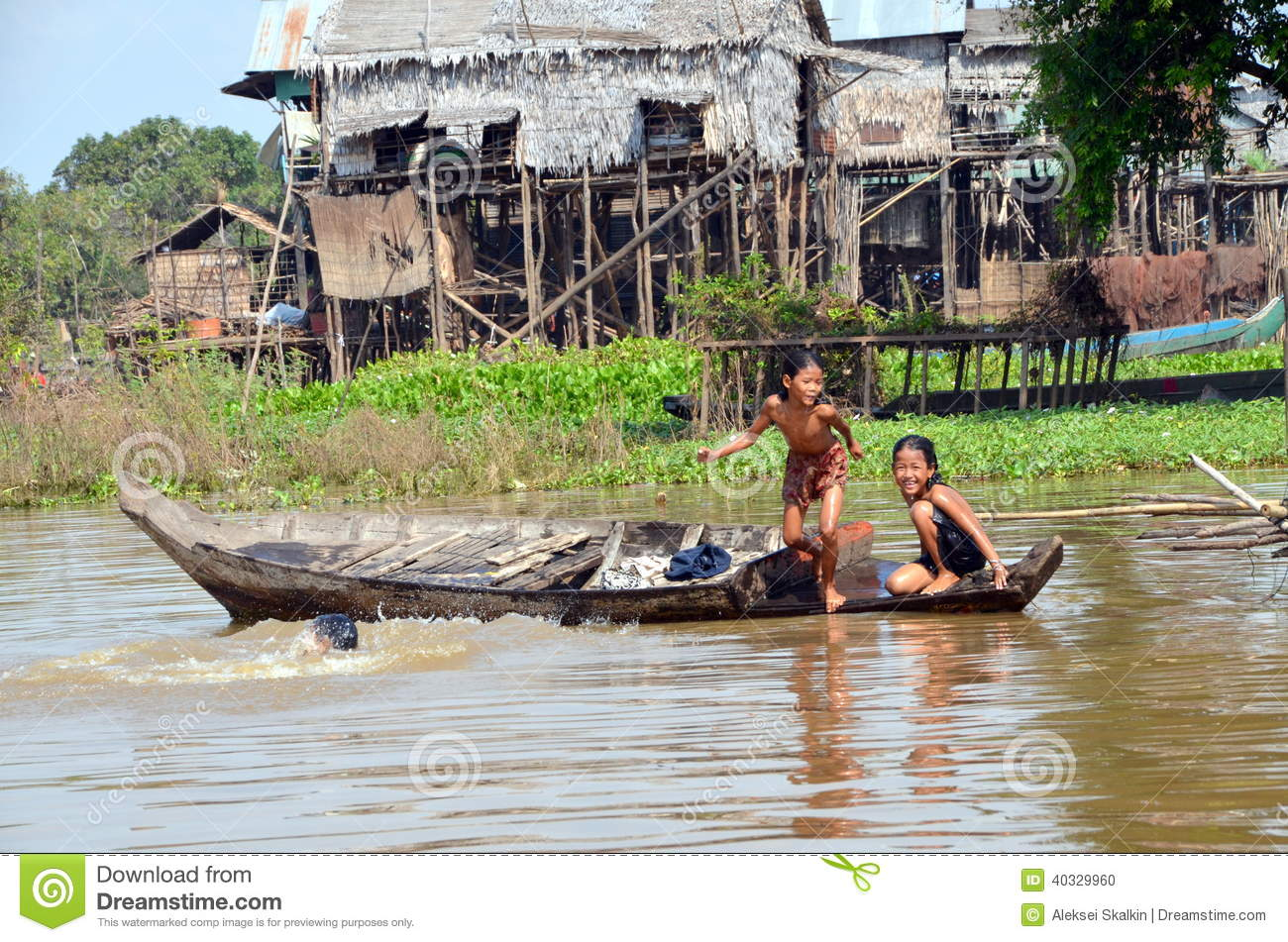 Children swimming in the murky waters of the Tonle Sap River, jumping ...