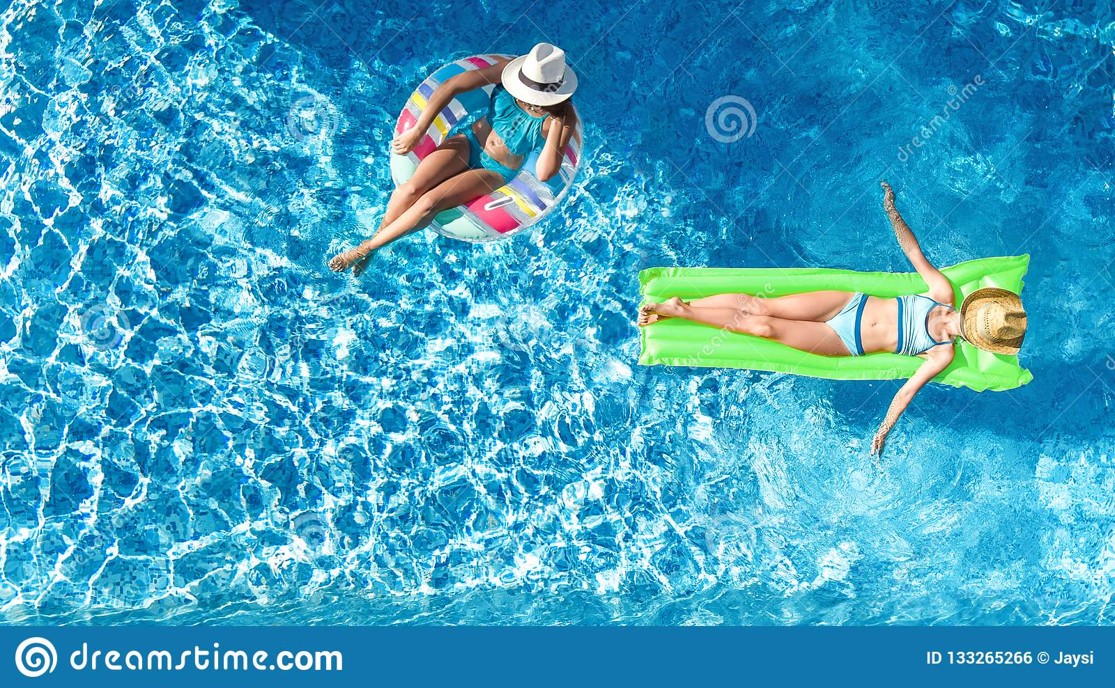 Children in swimming pool aerial drone view fom above, happy kids swim on inflatable ring donut and mattress, girls have fun