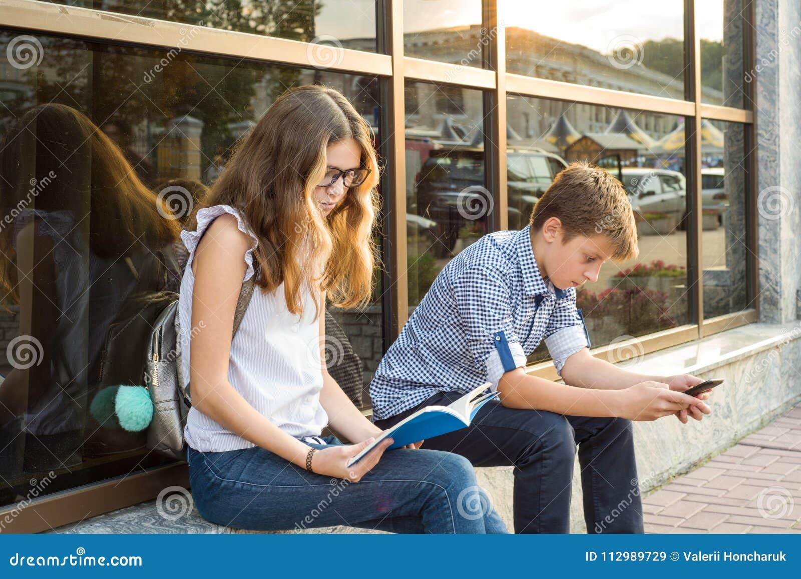 Children teenagers, break reading book and using smartphone.