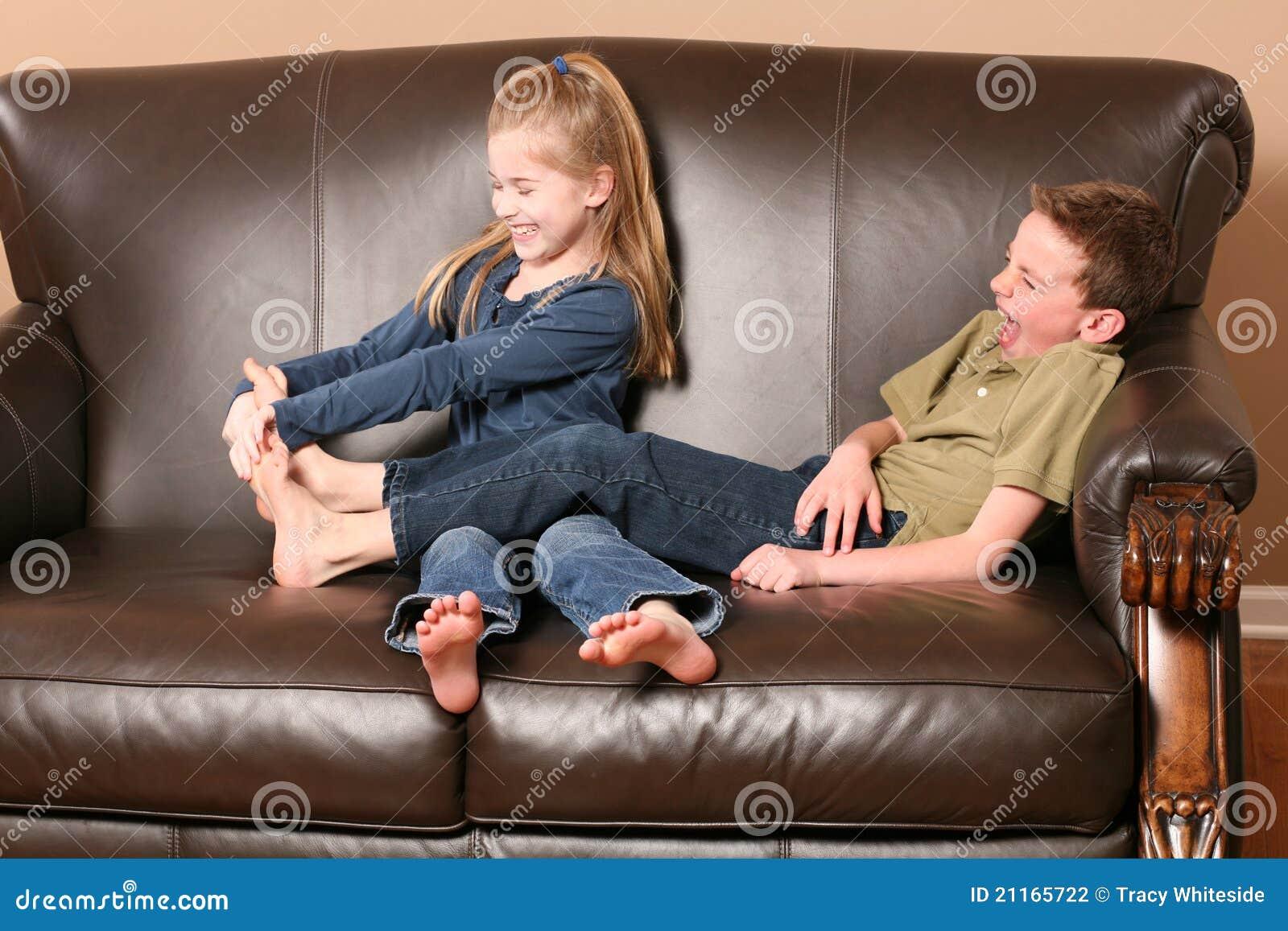 Cute little girl tickling brother's feet.