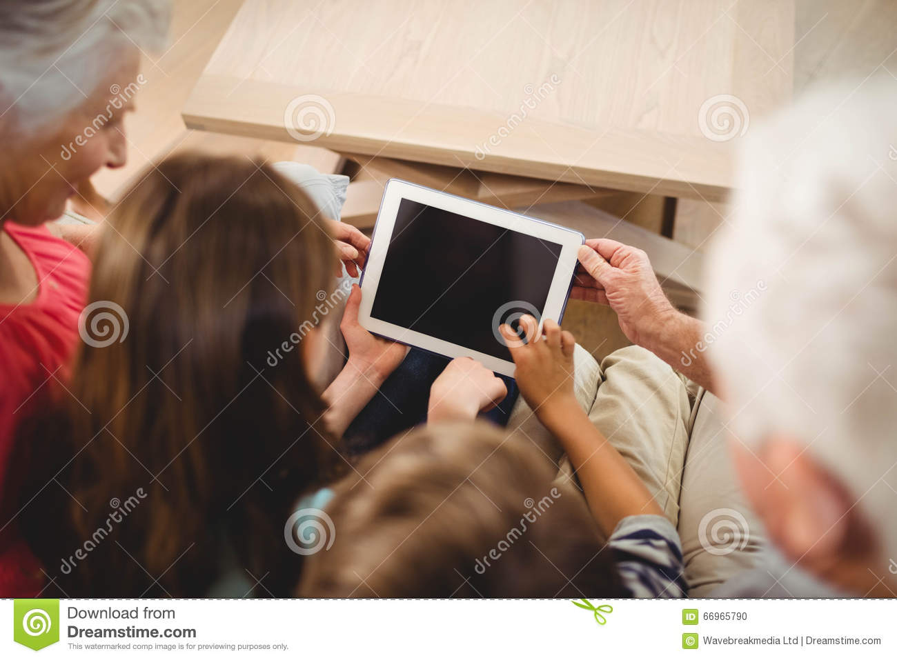 Children using tablet with their grandparents
