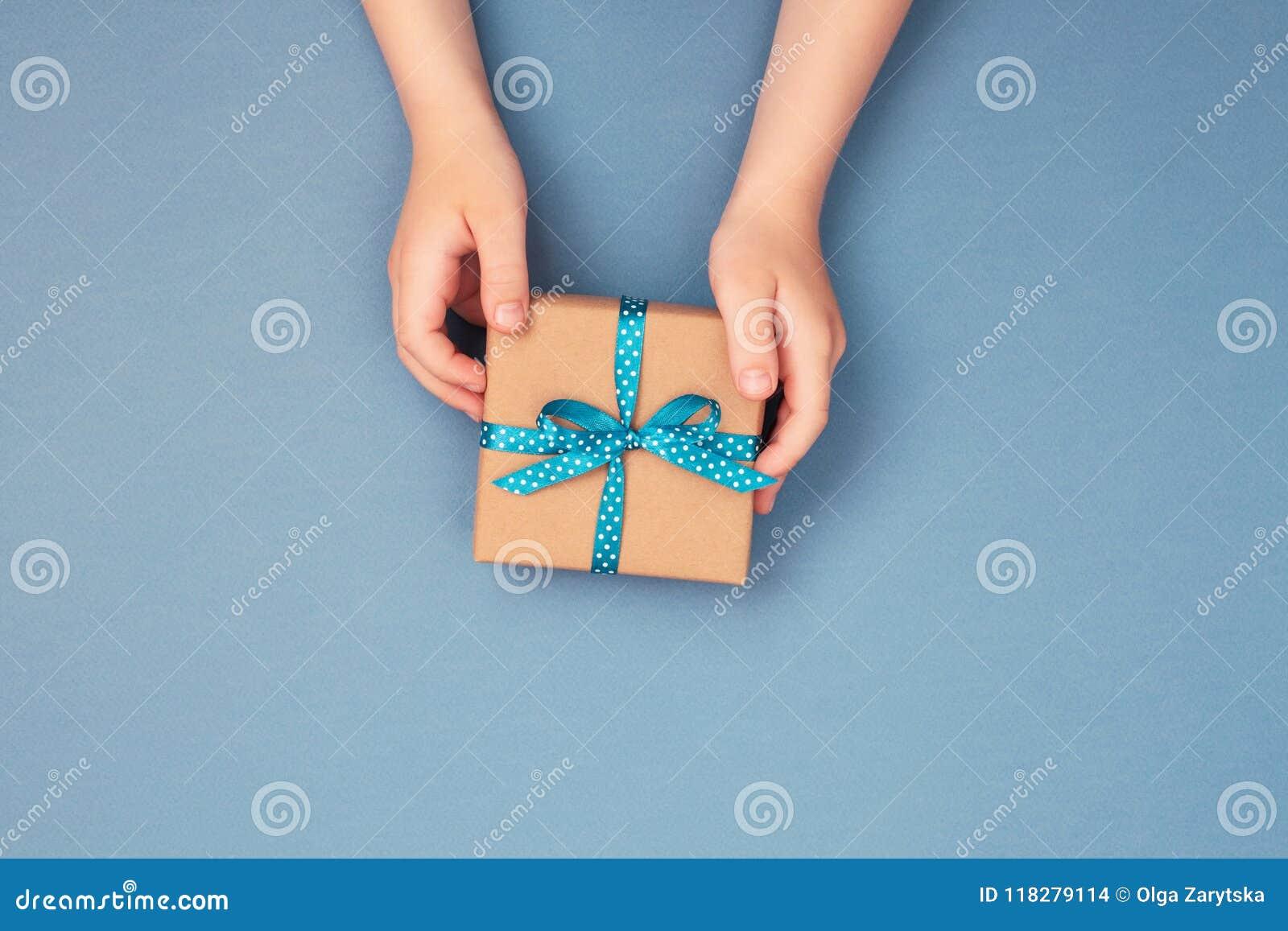 Childs räcker att rymma en gåvaask slågen in i kraft papper