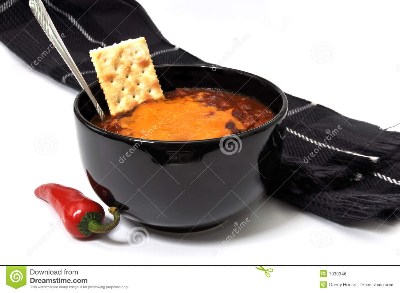 Bowl of chili with melted cheese, cracker, red cayenne pepper, spoon ...