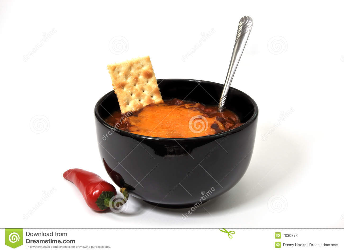 Bowl of chili with melted cheese, cracker, red cayenne pepper, and ...