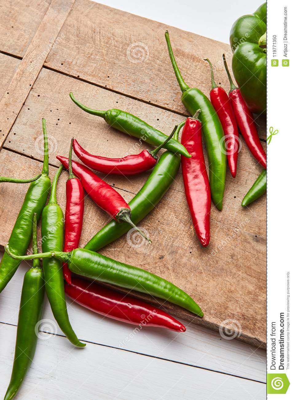 Chili colored peppers for cooking sauce on an old wooden board