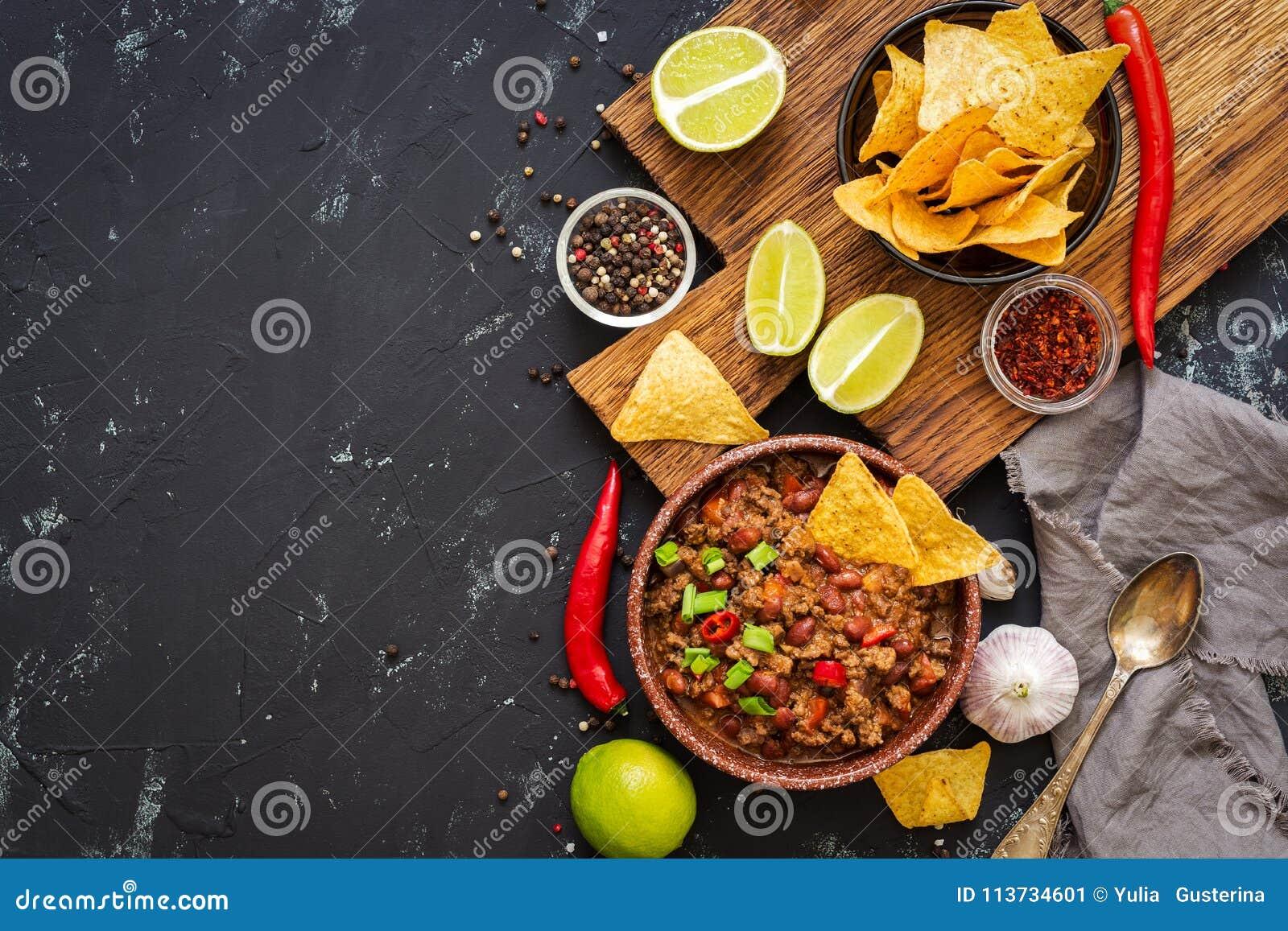 Chili con carne com as microplaquetas dos nachos no fundo rústico Alimento mexicano Lugar para o texto, vista superior