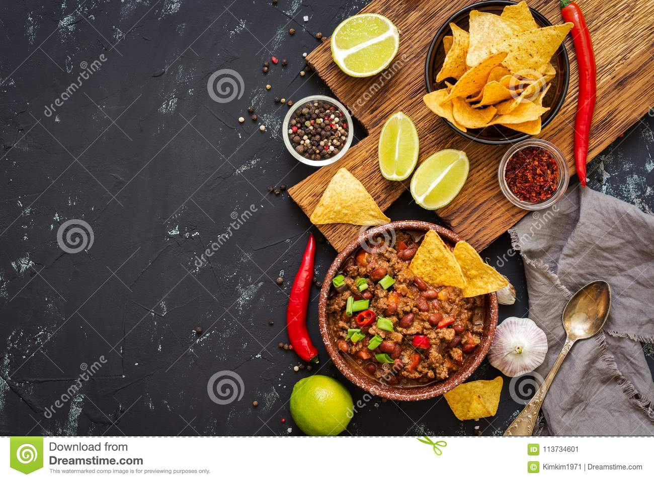 Chili con carne with nachos chips on rustic background.Mexican food. Place for text, top view.
