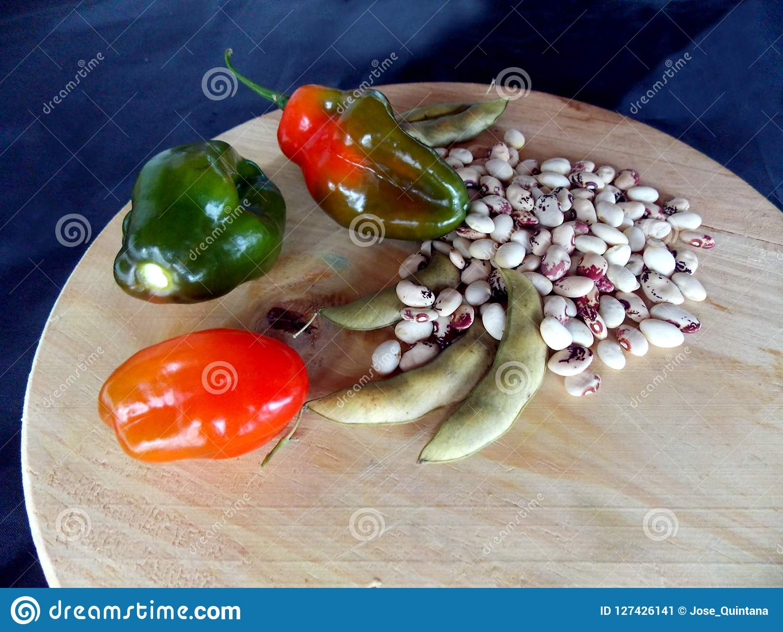 Chili Peppers, Beans And Pods Over A Wooden Cutting Board