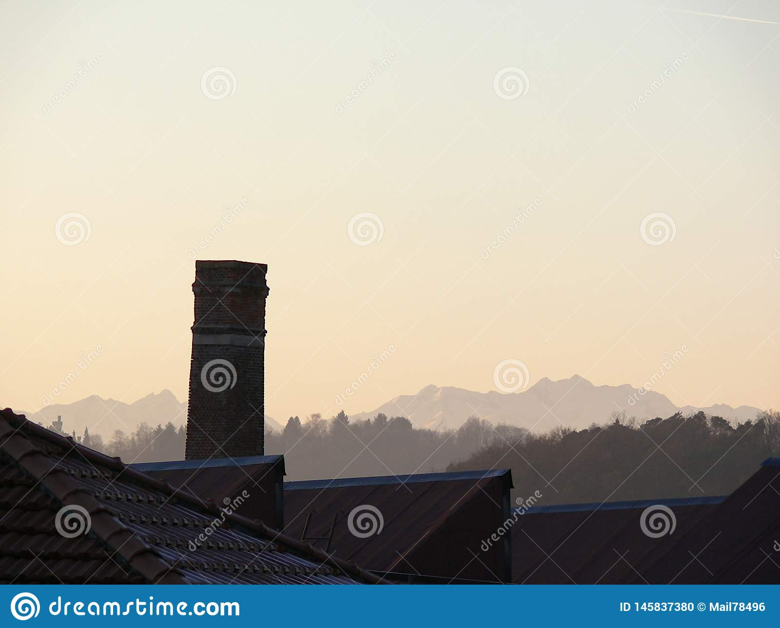 Chimney of old abandoned industrial complex. Work of industrial archaeology. In the background the profile of the mountains Alps