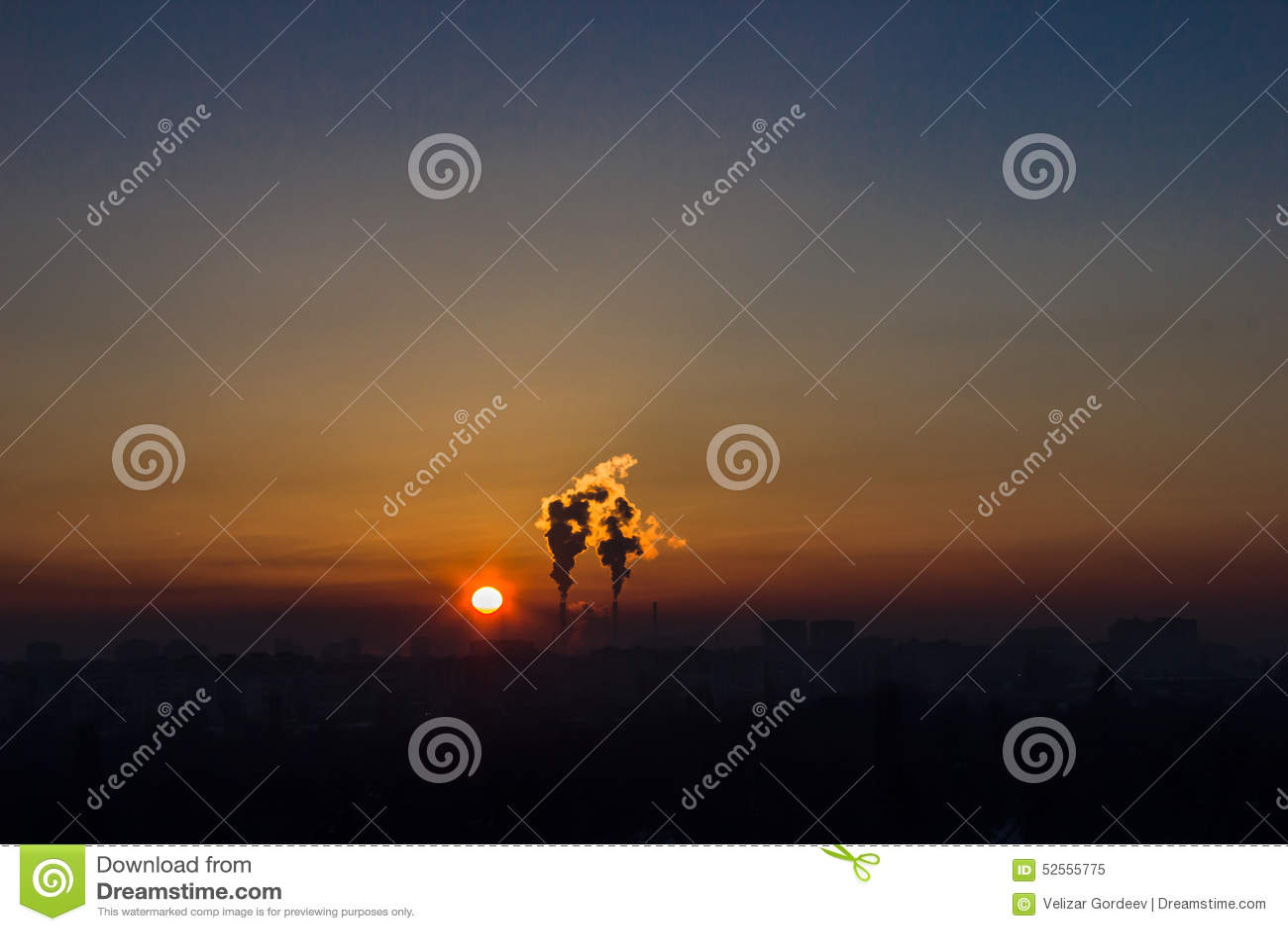 Chimneys and dark smoke over factory at sunset