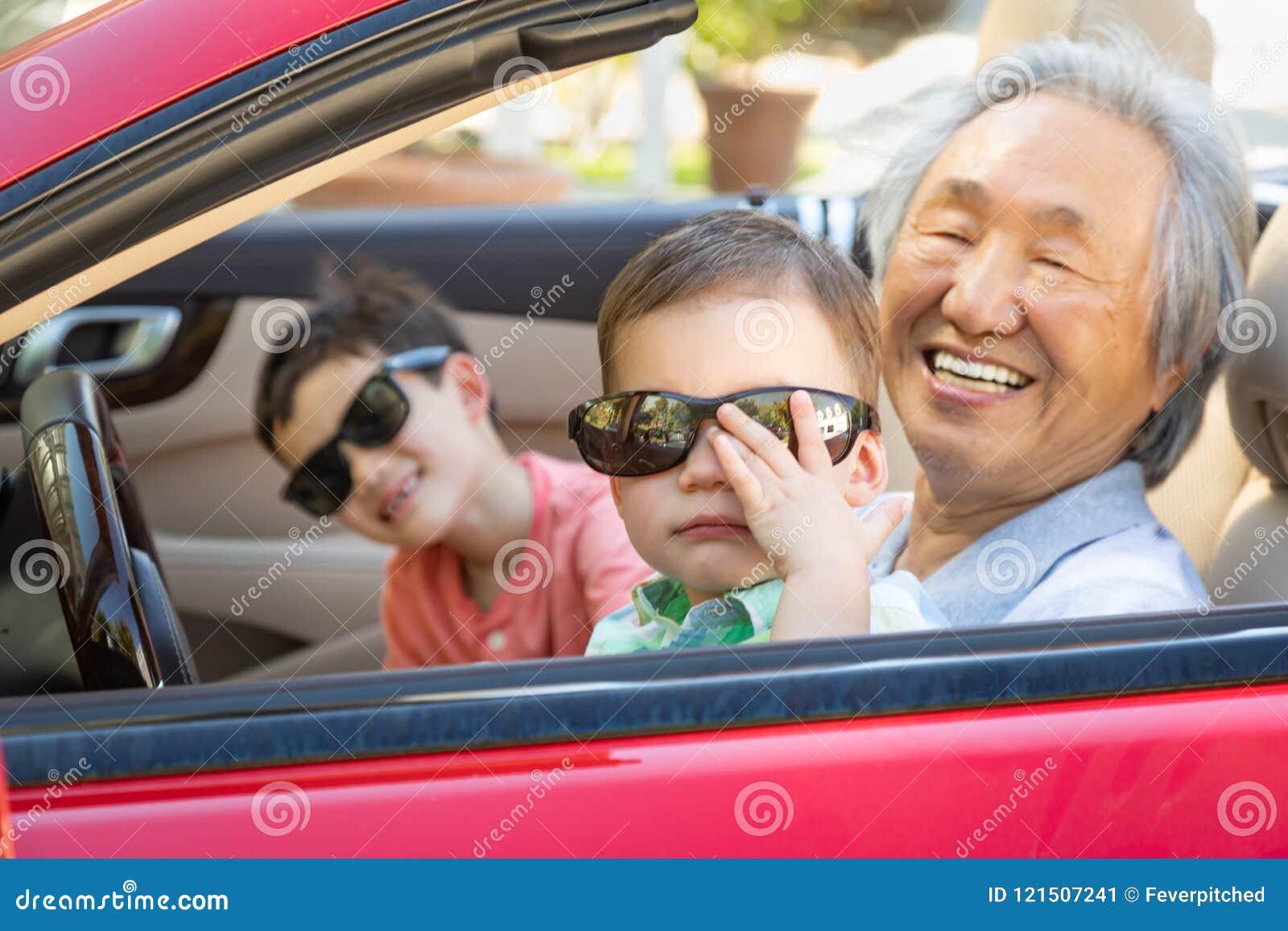 Chinês Granfather e crianças da raça misturada que jogam no carro estacionado