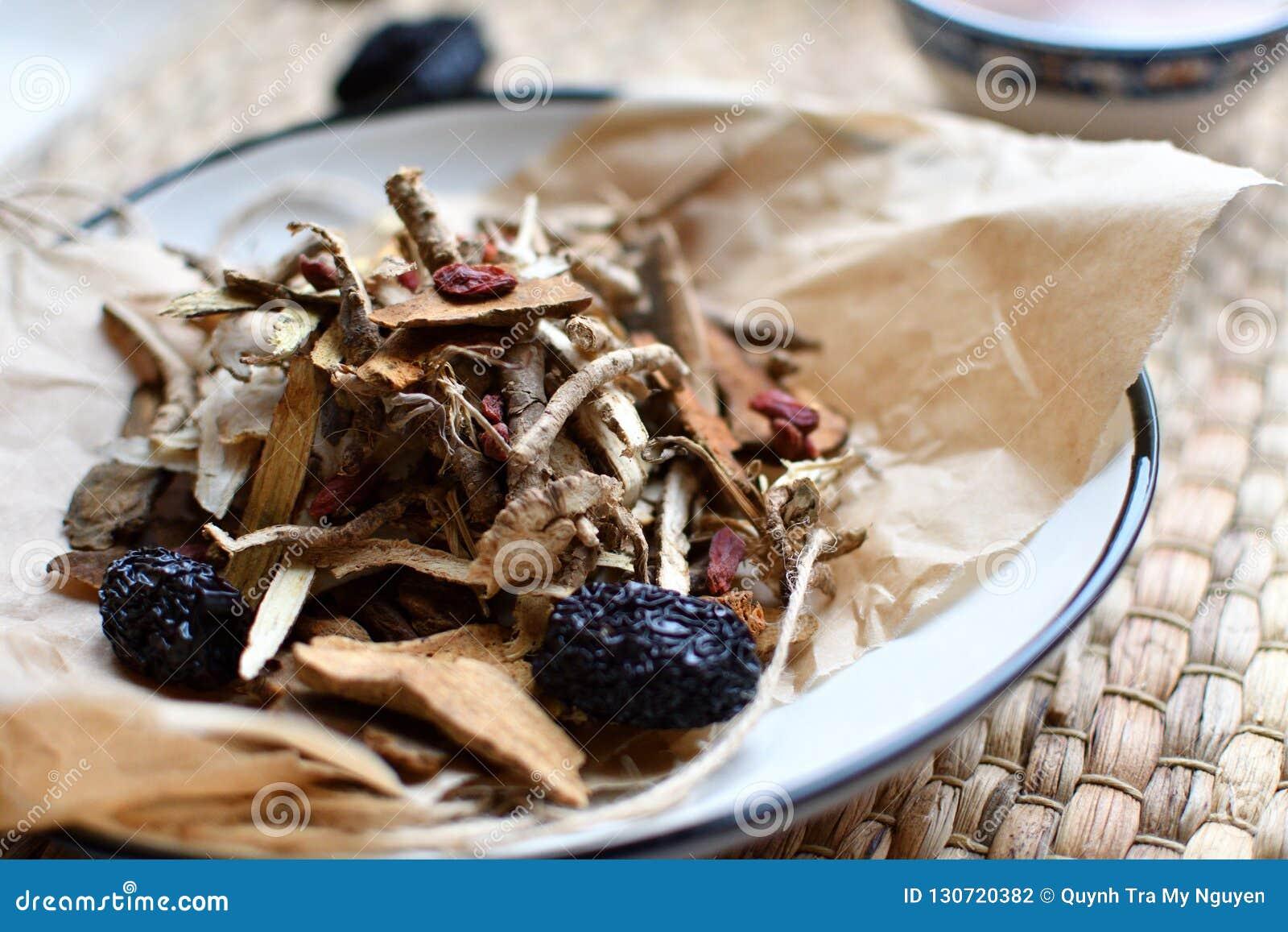 Chinees traditioneel geneeskundemanuscript Aftreksel met jujubes, gojibessen, gingseng wortels en anderen op perkamentdocument op